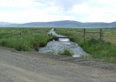 Dirt road in foreground with Stillwater ditch leading towards mountains in background.