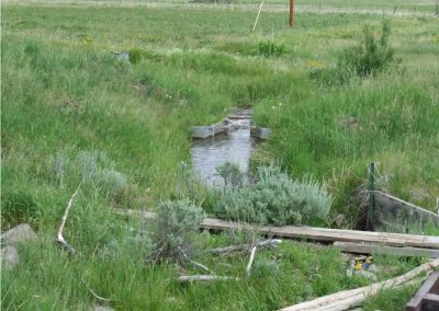 Small ditch running through grassy field.