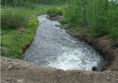 View from dirt road looking down onto ditch as water comes out of culvert.