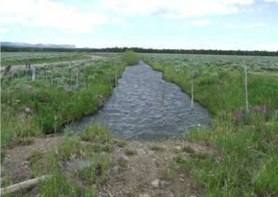 Stillwater ditch with old ranching fence going across ditch.
