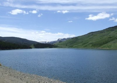 Yamcolo Reservoir along dam road with white capped mountains in background.